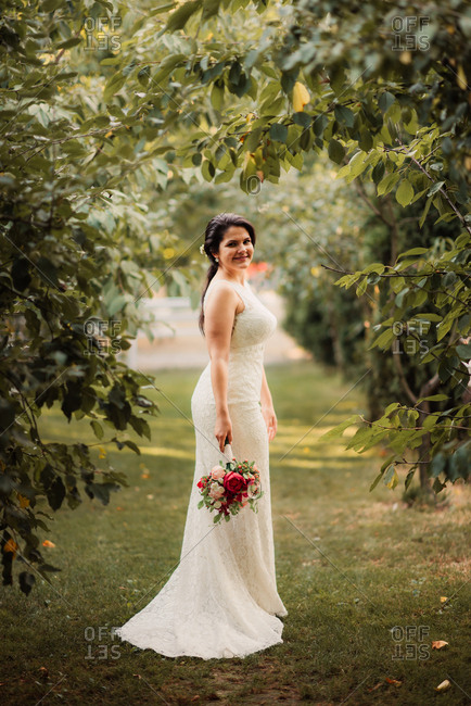 Portrait of a bride holding bouquet in an orchard