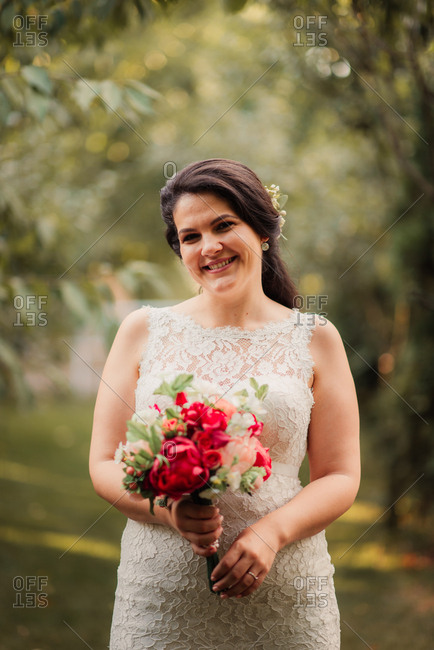 Portrait of a bride holding a pink and red peony bouquet