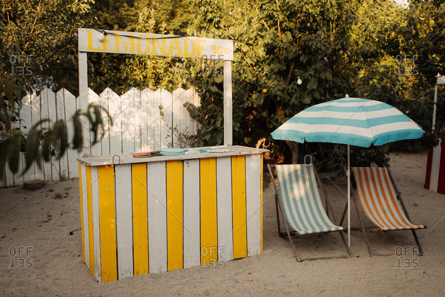Lemonade stand on a beach with lounge chairs