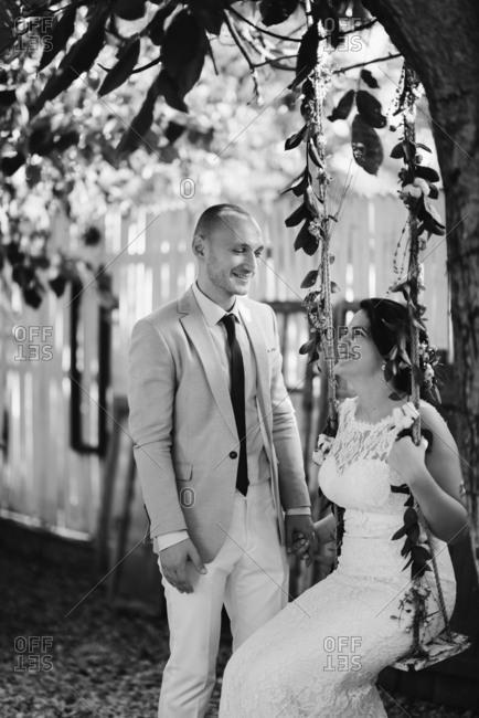 Groom watching bride swing on a tree swing