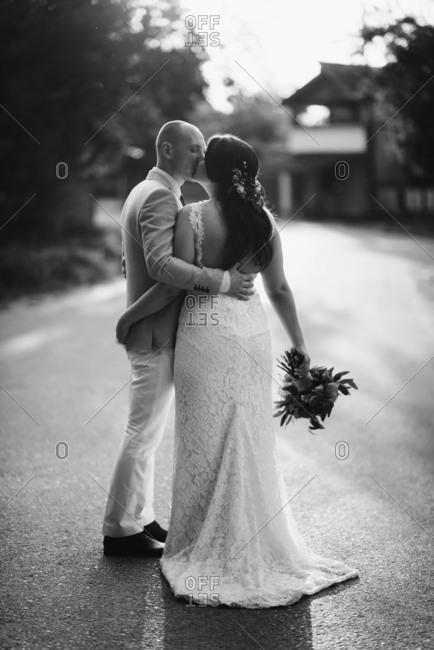 Portrait of bride and groom kissing in black and white