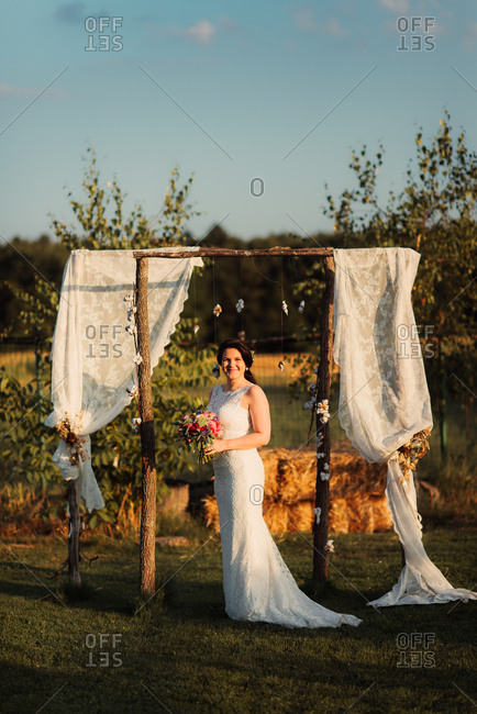 Happy bride standing under wedding arbor in the countryside