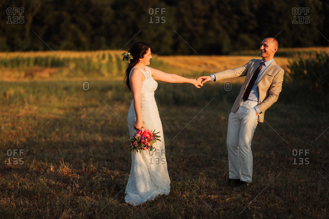 Bride and groom holding hands in a country field