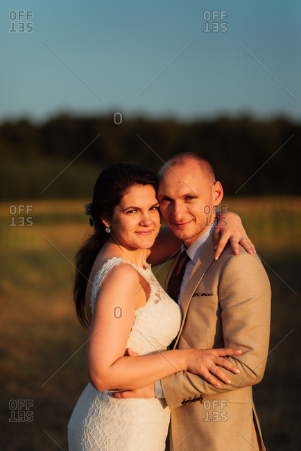 Newlywed couple embraced in a country field