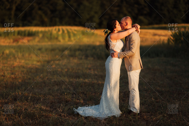 Newlywed couple kissing in a country field