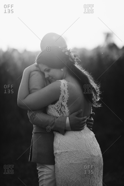 Black and white portrait of bride and groom hugging