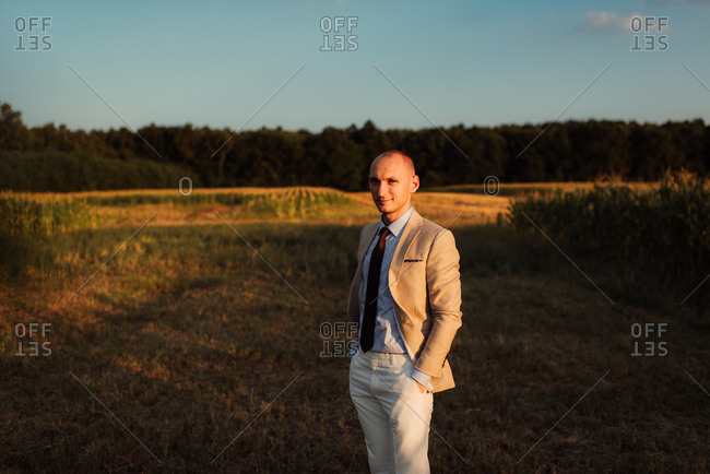 Portrait of a groom in a country field at sunset