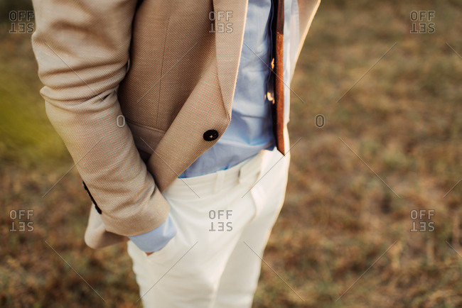 Close up of a groom standing with hands in his pockets