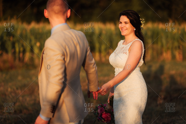 Groom holding hands with his bride in a country field