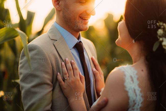 Newlywed couple together in a cornfield at sunset