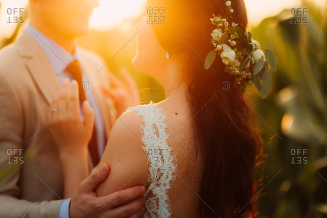 Groom and bride standing in a cornfield at sunset