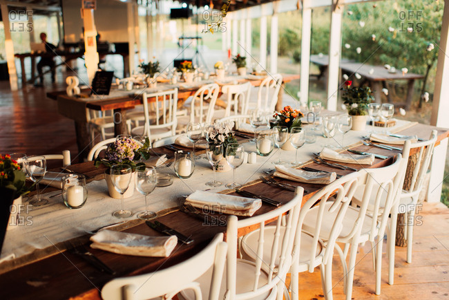 Rustic tables with burlap table runner at a wedding reception