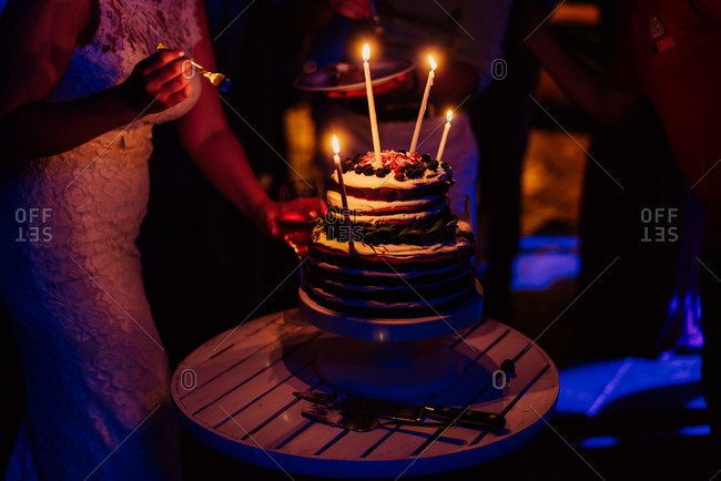 Bride standing by lit cake