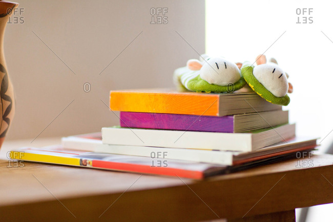 Children's and baby's board books stacked on table with animal socks