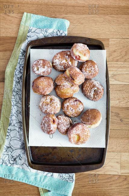 Freshly baked jelly filled doughnuts on baking sheet