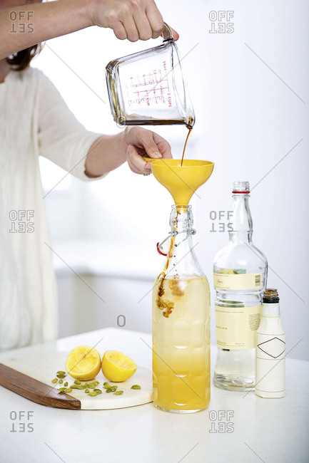 Person pouring from a glass measuring cup into a funnel to create drink with lemon and pistachios