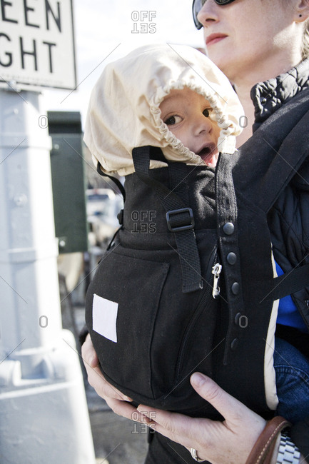 Baby boy in baby carrier on street covered from sun