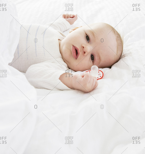 Baby boy on adult bed without pacifier in mouth