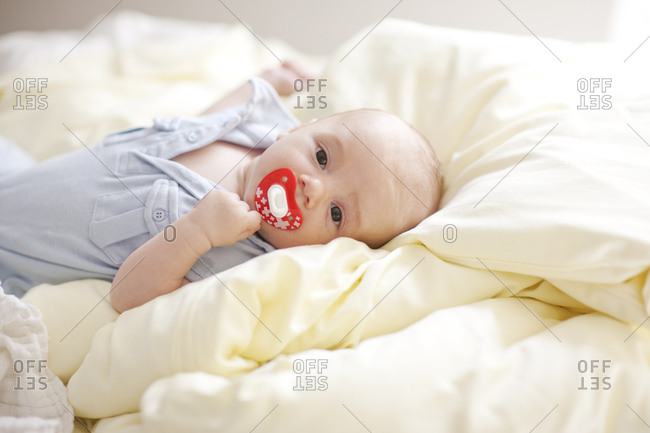 Baby boy with on adult bed with pacifier