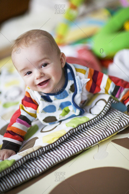 Baby boy on belly playing on quilt in play room