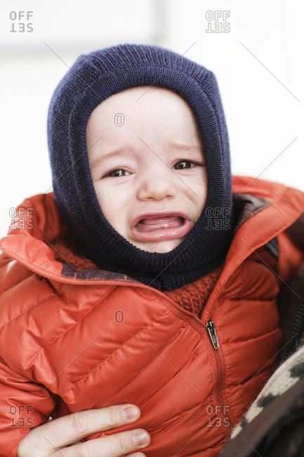 Baby boy crying in winter coat and hat