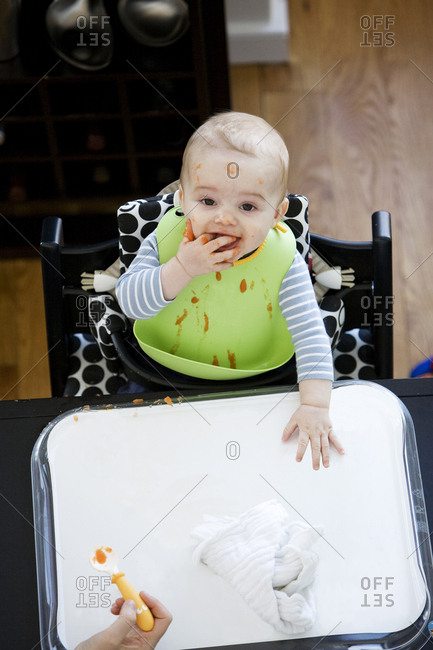 Baby boy messy eating with bib