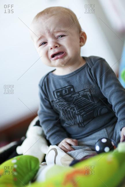 Baby boy crying in playroom