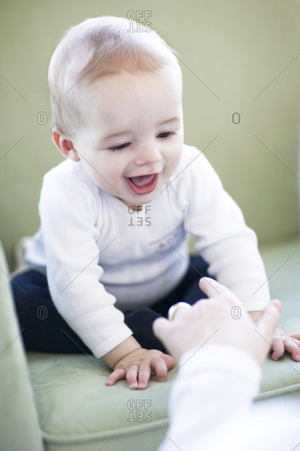 Baby boy smiling on rocking chair playing with adult poking finger at him