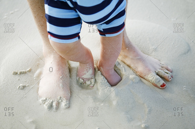 Baby boy feet and moms feet covered in sand on beach