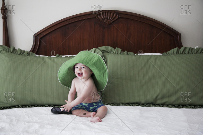 Baby boy laughing on bed in swim trunks with green adult sun hat on head
