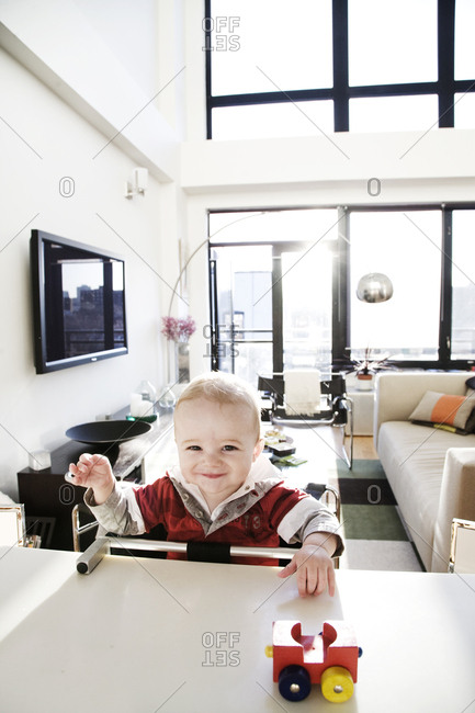 Baby boy smiling and playing with toy at adult table in penthouse