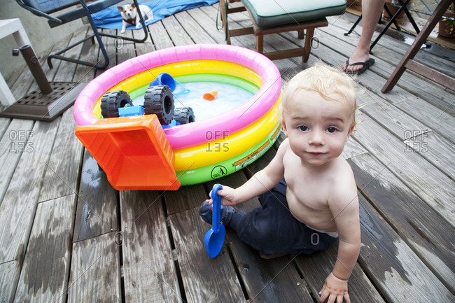 Baby boy playing next to kiddie pool on deck
