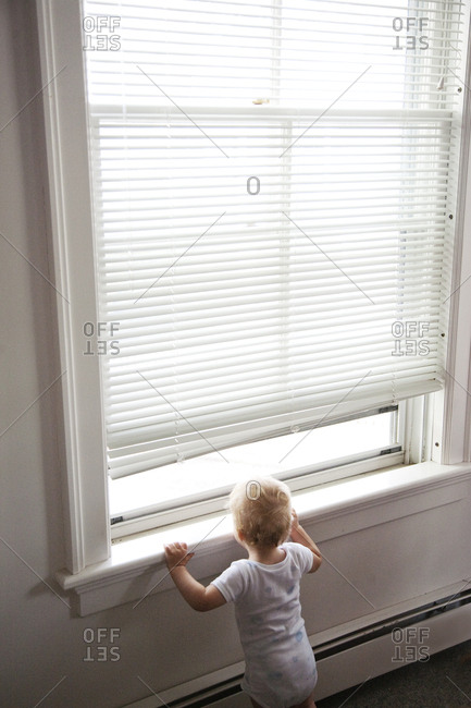 Baby boy looking out window under blinds