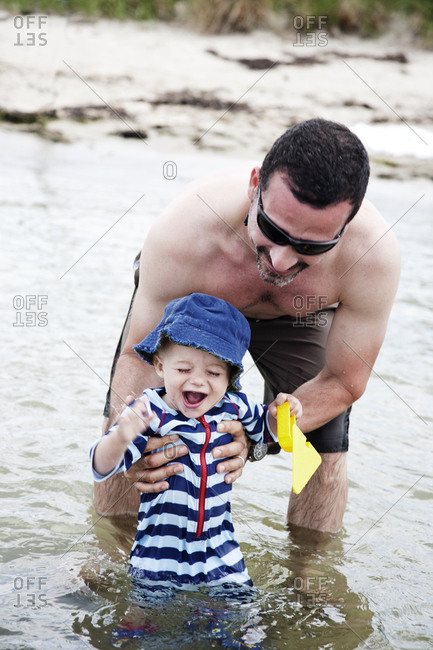 Baby boy in water playing with dad