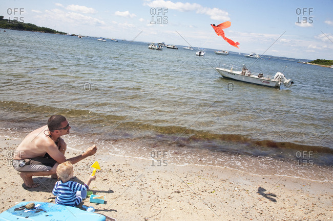 Baby boy playing on beach with kite and father with boat in background