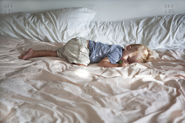Baby boy in sleeping in adult bed face down