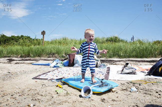 Baby boy crying on beach on surfboard