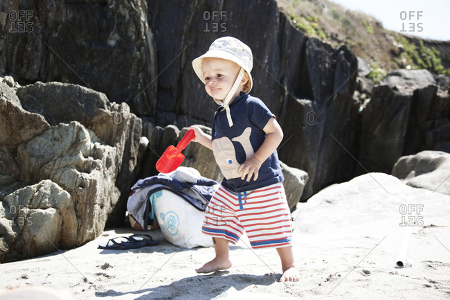 Baby boy playing on beach with shovel, France