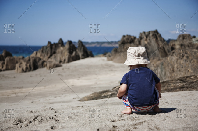 Baby boy playing on beach facing away from camera, France