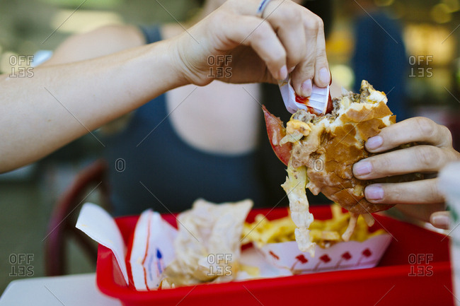 Female eats burger at In and Out restaurant in San Francisco California