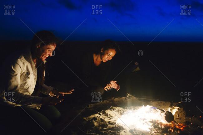 Female laugh and chat at beach bonfire in San Francisco, California
