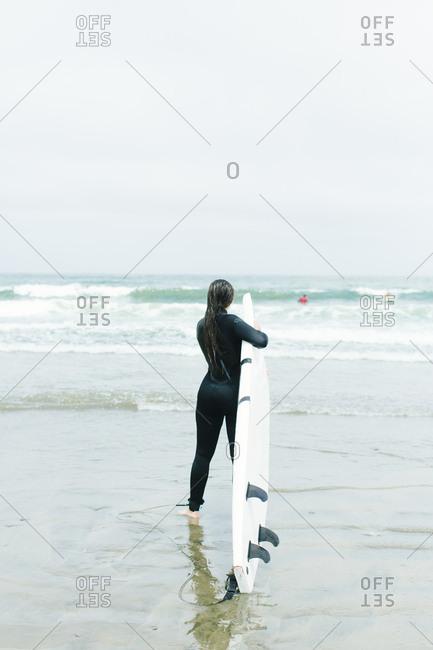 Female walks into ocean to surf in San Francisco, California