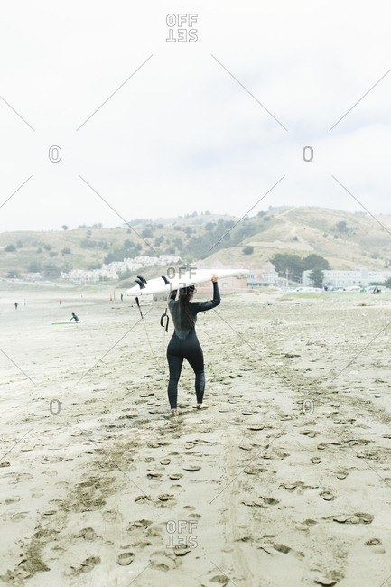 Female walks into ocean to surf in San Francisco, California