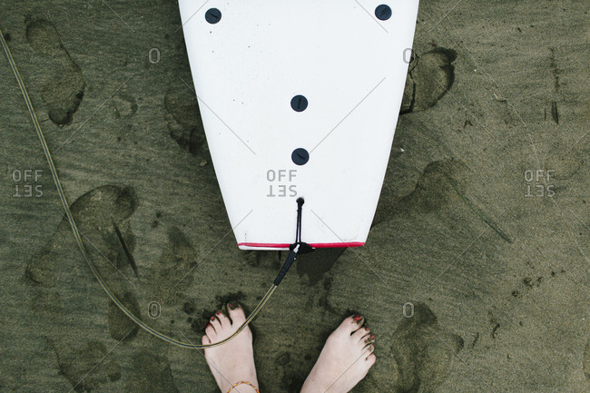 Still life of surf boards on sand with feet in San Francisco, California