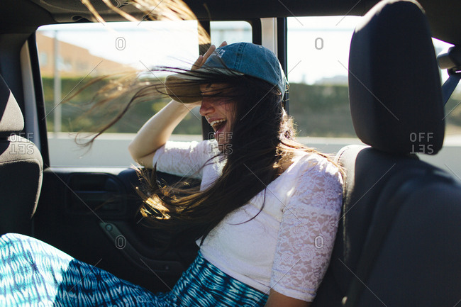 Female laughs while her hair blows around in open top jeep on California road trip