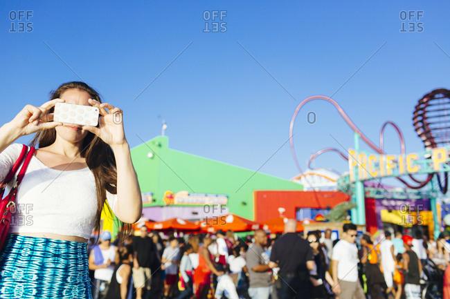 Santa Monica, California, USA - June 20, 2015: Female takes photo at Pacific Park in Santa Monica Pier, Santa Monica, California