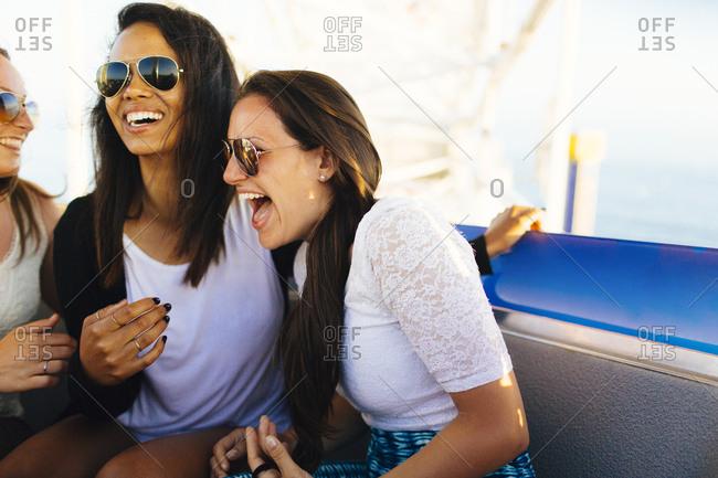 Females laugh together on ferris wheel in Pacific Park in Santa Monica Pier, Santa Monica, California