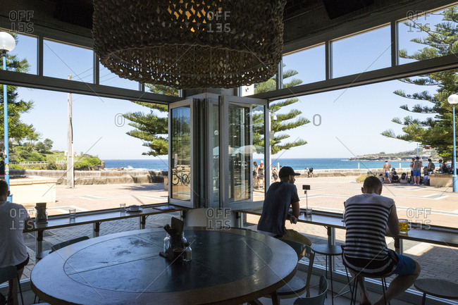 Sydney, Australia - February 24, 2017: People seated at bar open to the outside with a view of the ocean