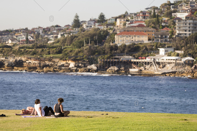 Sydney, Australia - February 24, 2017: People relaxing on grassy bluff above Coogee Beach