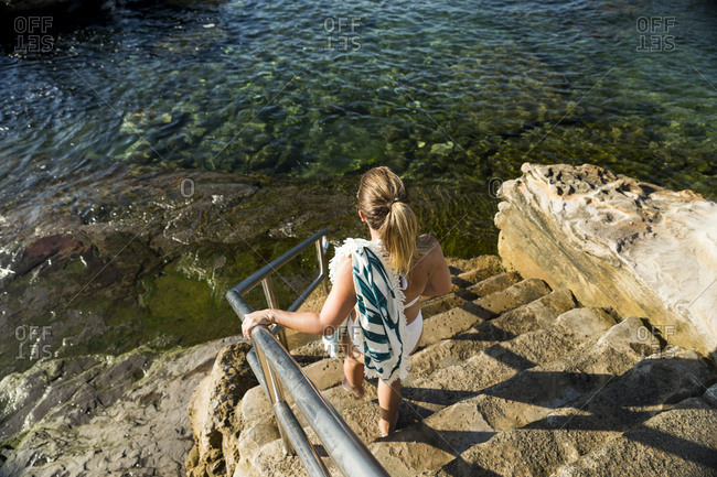 Young woman walking down stairs to swimming area at Coogee Beach in Sydney, Australia